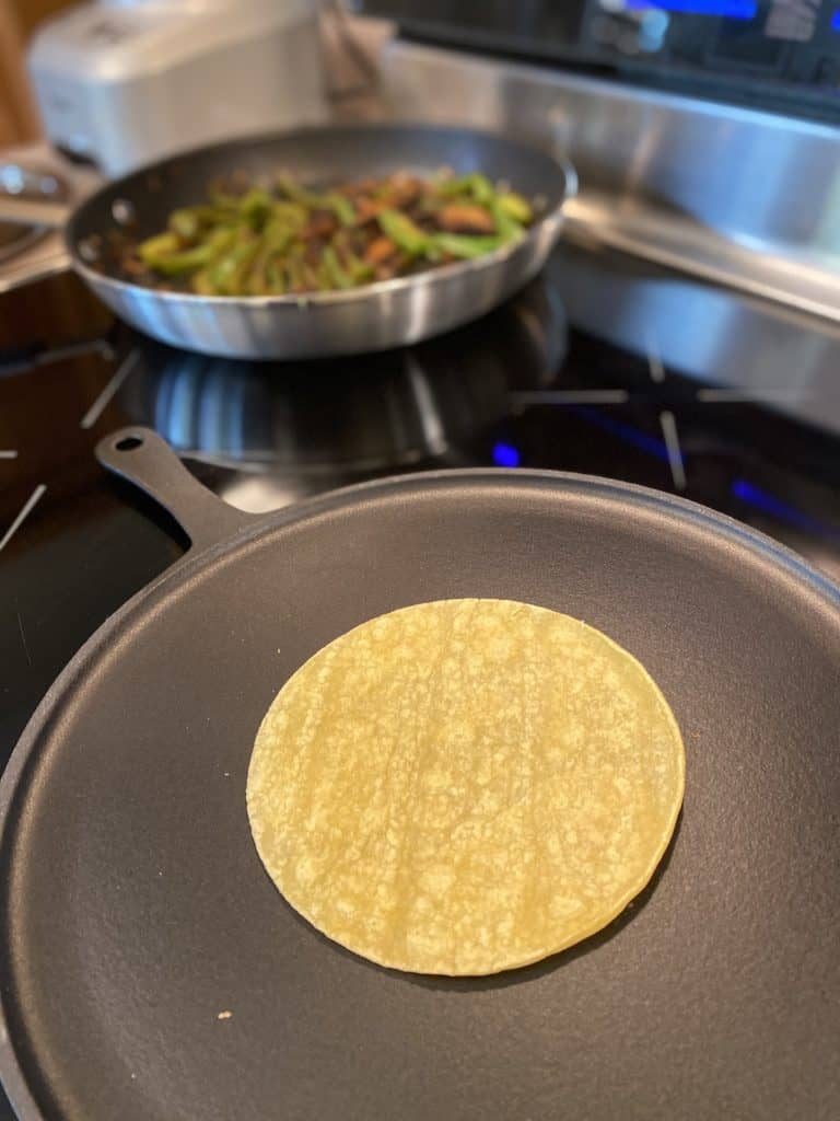 heating corn tortilla on a pan while vegetables are kept warm