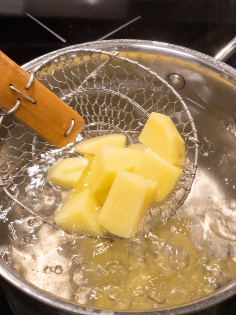 Diced yellow potatoes boiling