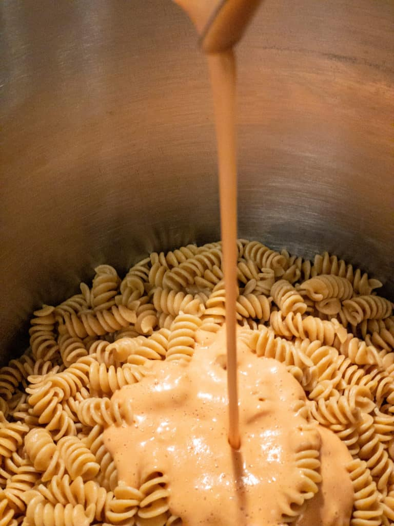 Pouring Fire Roasted Pasta Sauce over pasta in a pot