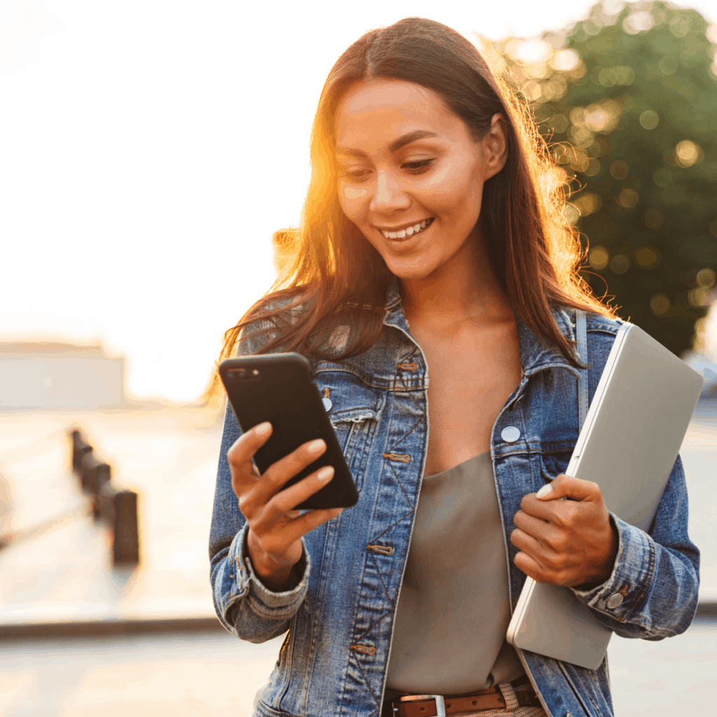 woman holding iphone and laptop