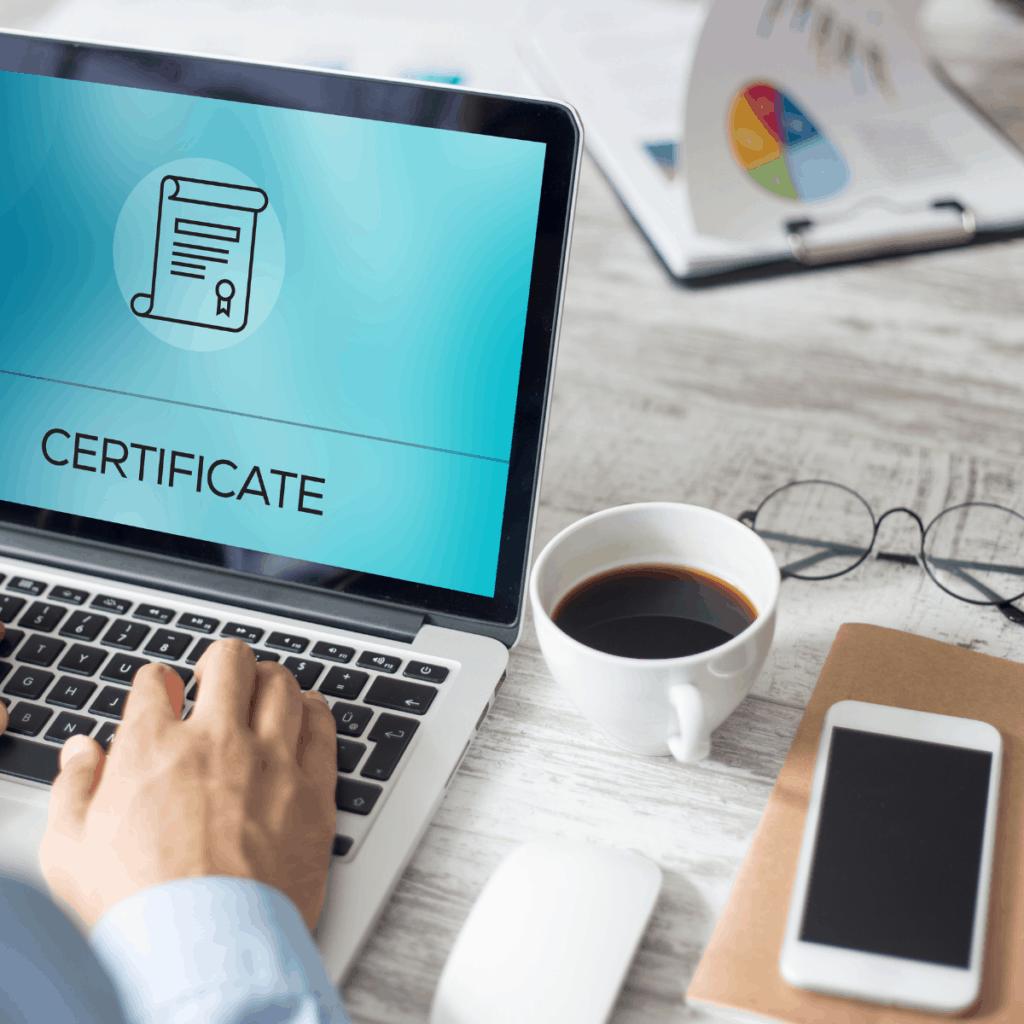 laptop hand coffee phone word certificate on screen