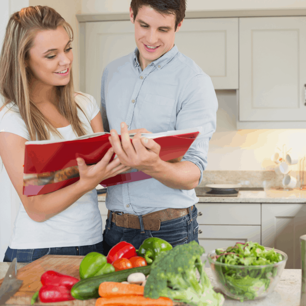 couple holding cookbook in front of vegetables