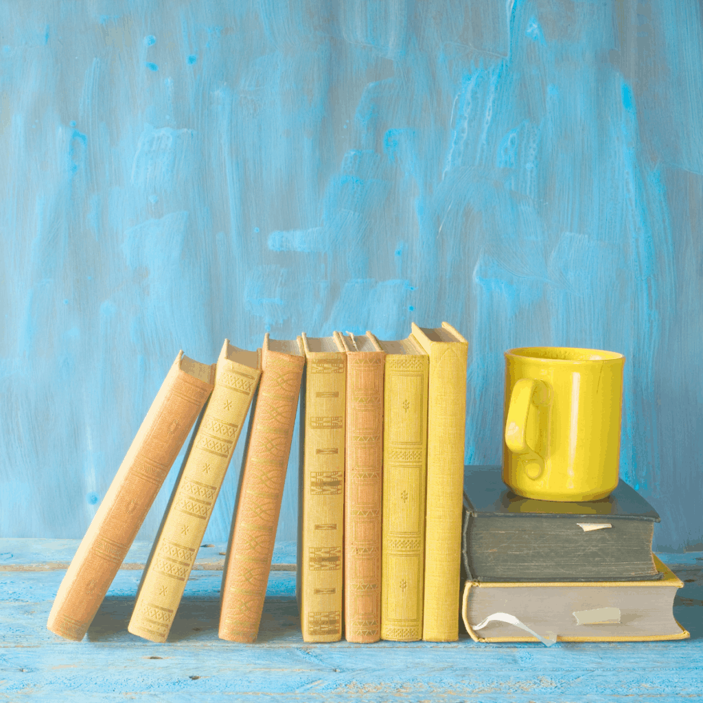 yellow books with yellow coffee mug on a blue background
