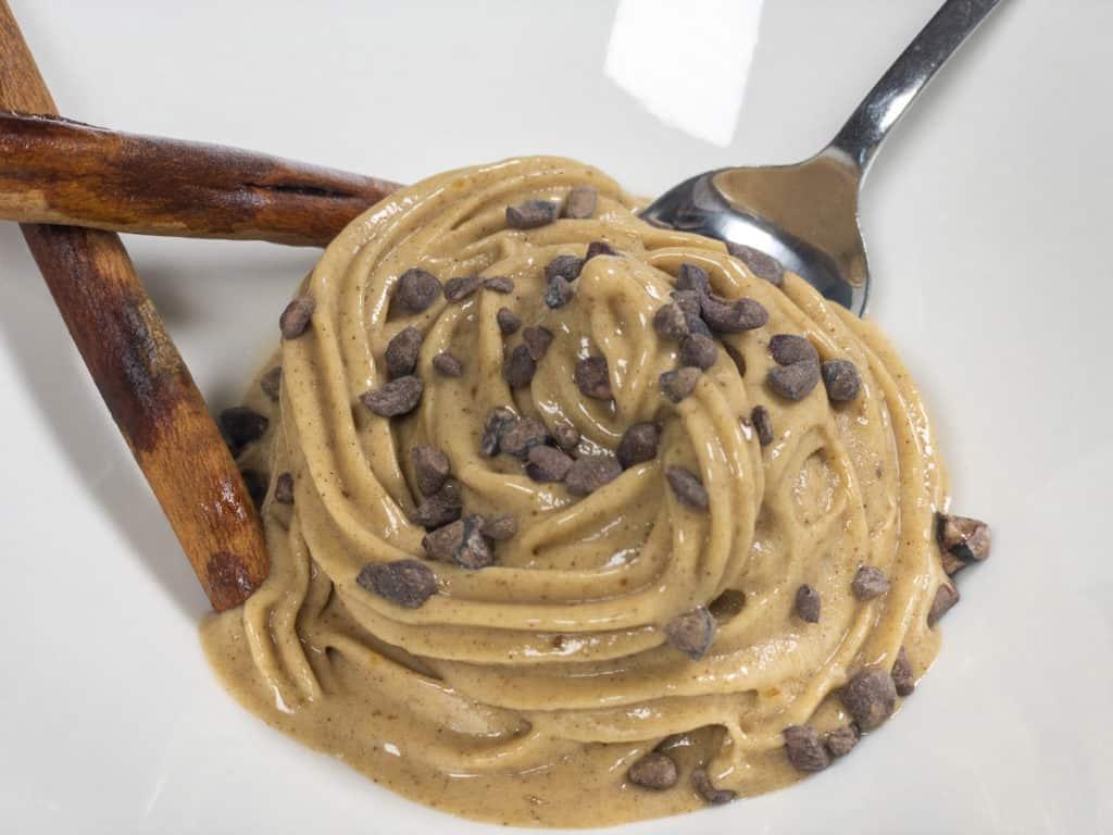 Cinnamon Bun Nice Cream In bowl with cacao nibs, cinnamon sticks, and spoon