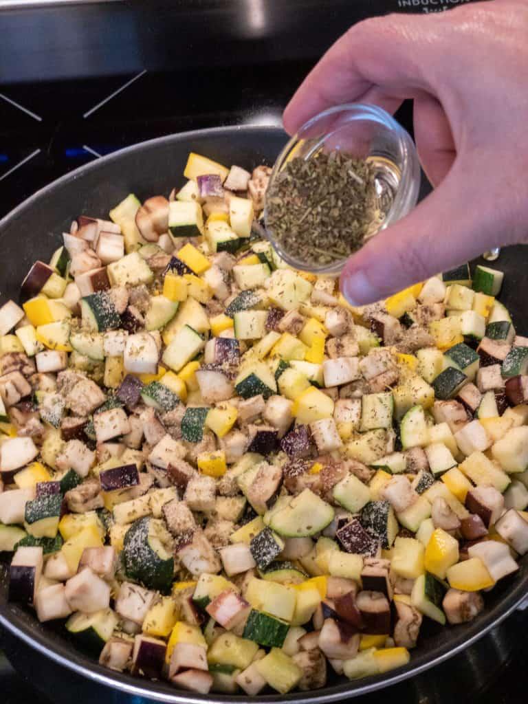 adding Italian seasoning to easy ratatouille in pan