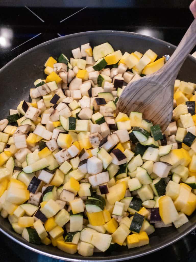 stirring easy ratatouille vegetables in pan
