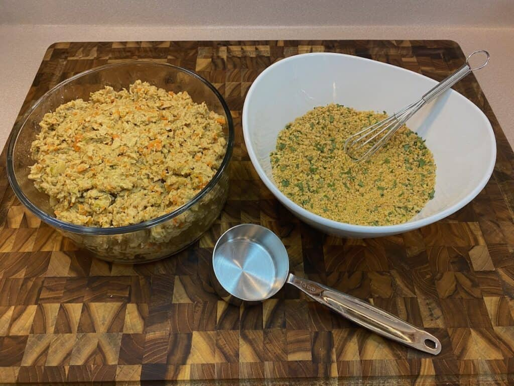 wfpb crab cake burger mixture and breading mixture with ⅓ cup measuring cup on wooden cutting board
