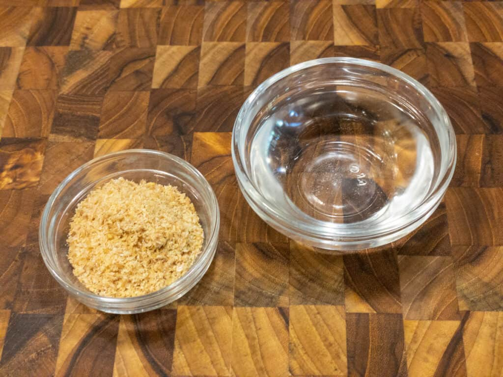 ground flax and water in separate small glass bowls on wooden cutting board