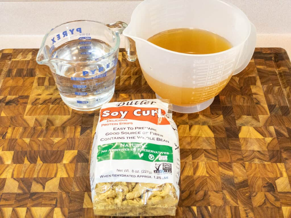 Soy curls in bag, 4 cups vegetable broth, and 2 cups water on cutting board