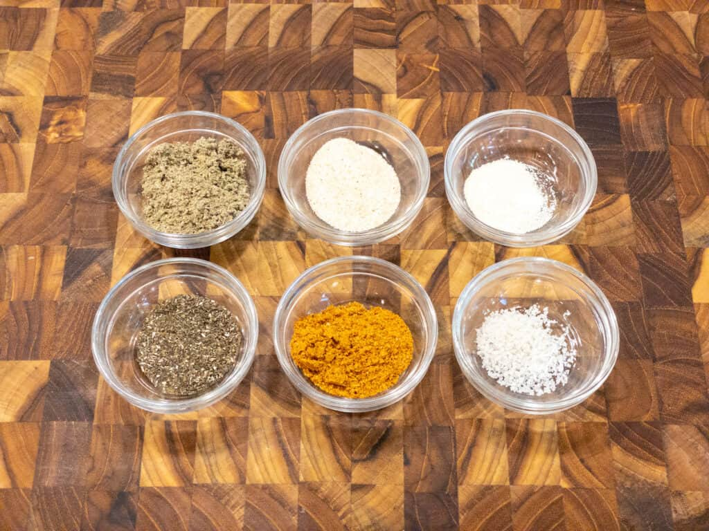 Veggie spices in small glass bowls on wooden cutting board