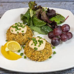 Soy curl crab cakes on a white plate with lemon wedges red grapes and greens