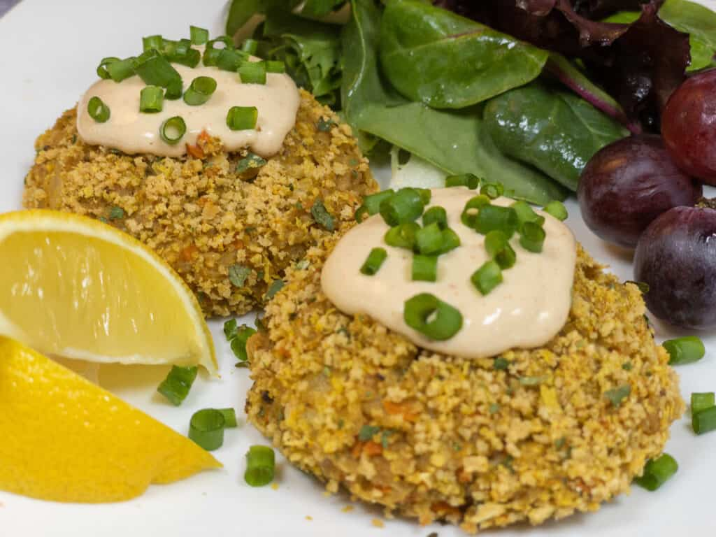wfpb soy curl crab cakes closeup on plate with lemon wedges crab cake sauce minced chives red grapes and green salad on white plate