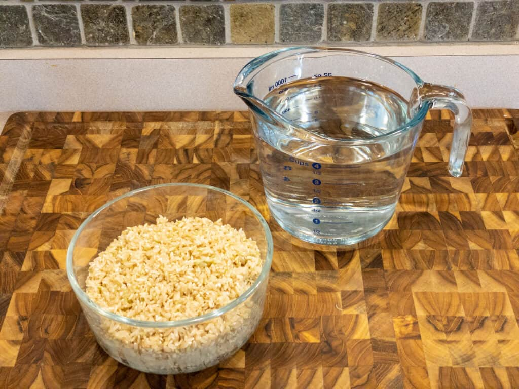 Two cups rinsed brown rice in clear glass bowl with four cups cold water in pitcher sitting on wooden cutting board.