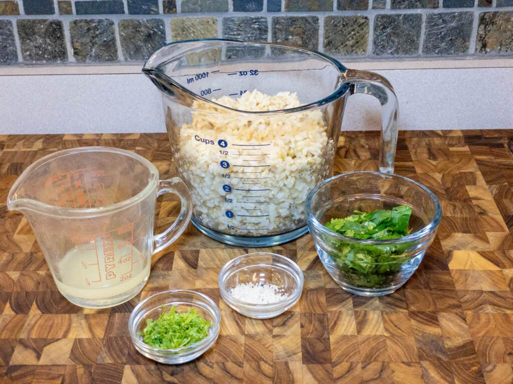 Cooked brown rice, lime juice, lime zest, sea salt, and chopped cilantro in glass containers on wooden cutting board.