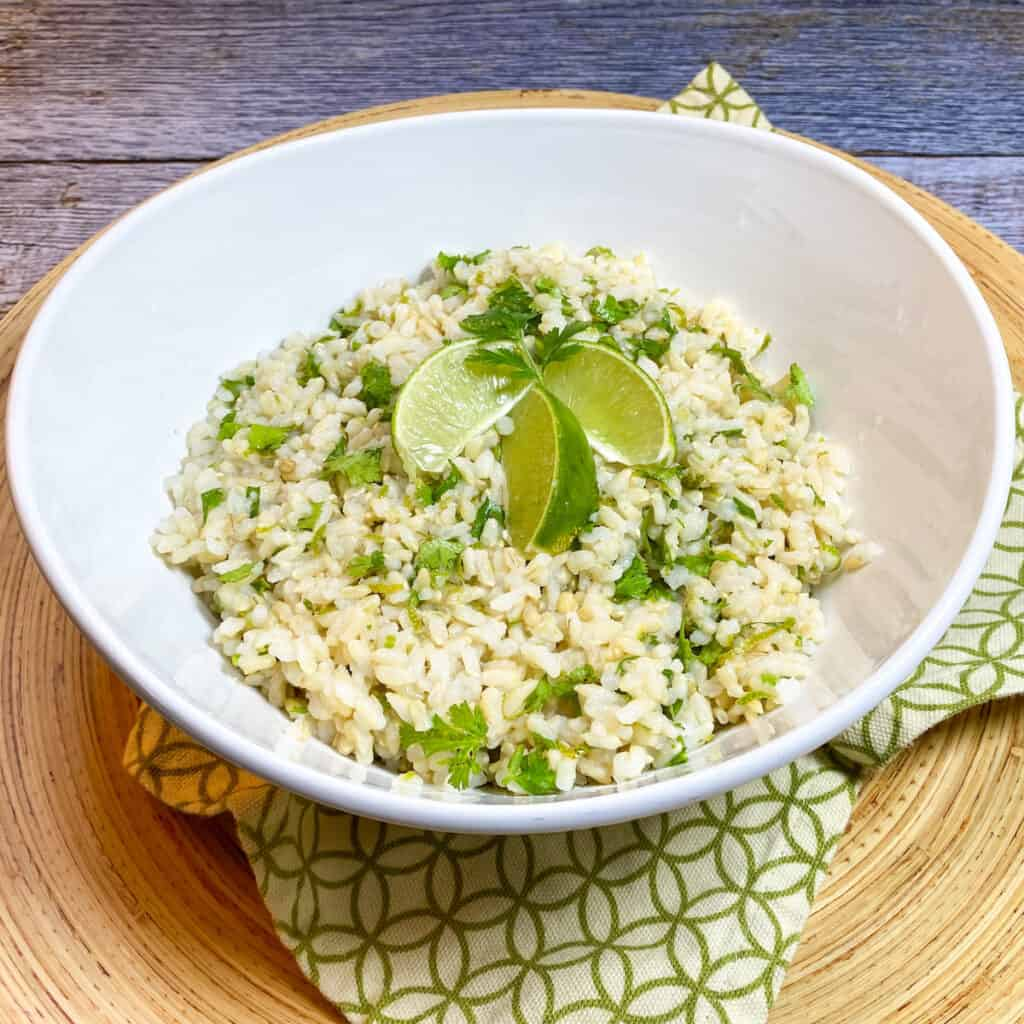 Cilantro Lime Brown Rice in White Bowl with Lime Wedges for Garnish.