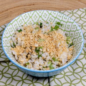 Cilantro Lime Brown Rice in Small Blue and Green Bowl with Garnish of Chopped Peanuts.
