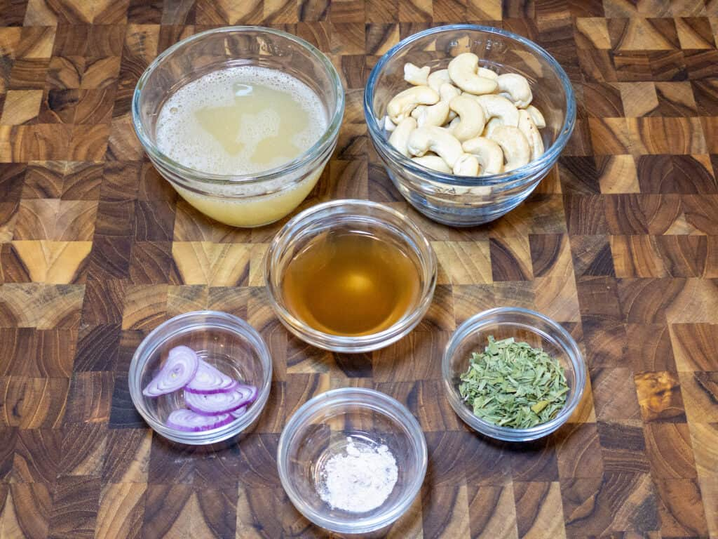 WFPB Bearnaise sauce ingredients in small clear glass bowls on wooden cutting board
