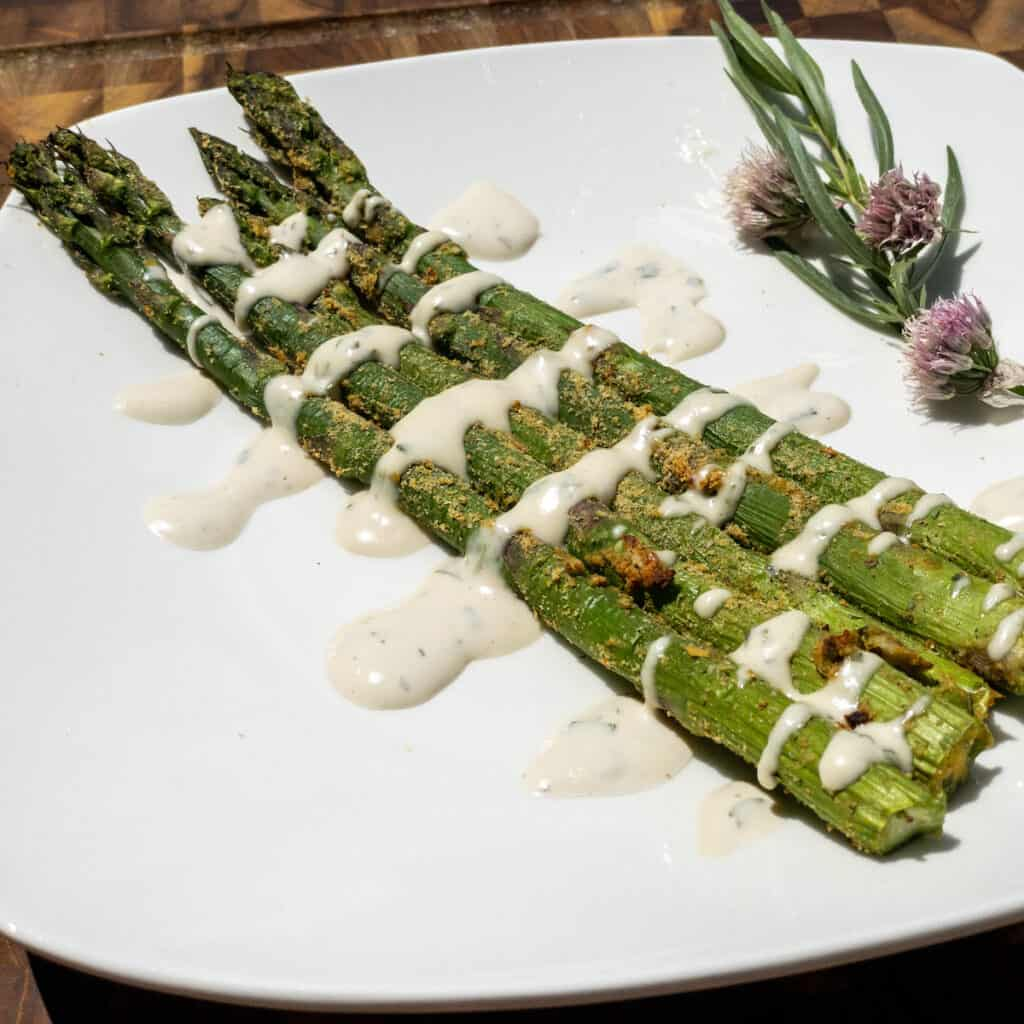 WFPB Oil-Free Air-Fried Asparagus on a white plate with WFPB Bearnaise sauce drizzled over top and a garnish of tarragon and chive flowers