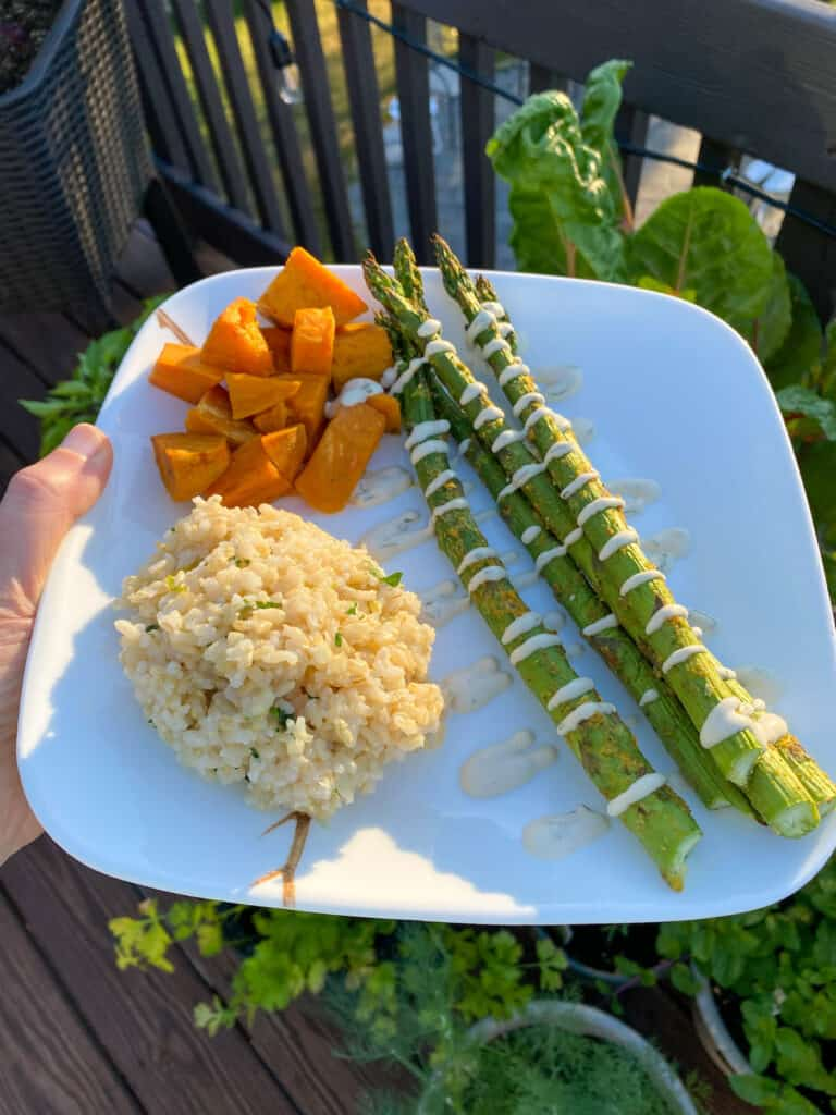 Asparagus with Bearnaise Sauce on plate with cilantro lime rice and roasted sweet potatoes