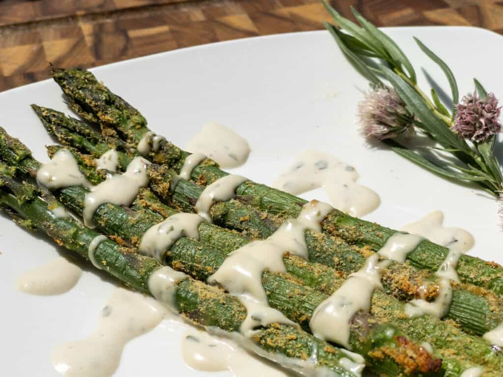 WFPB oil-free air-fried asparagus drizzled with Easy WFPB Bearnaise sauce on white plate garnished with fresh tarragon and chive blossoms.
