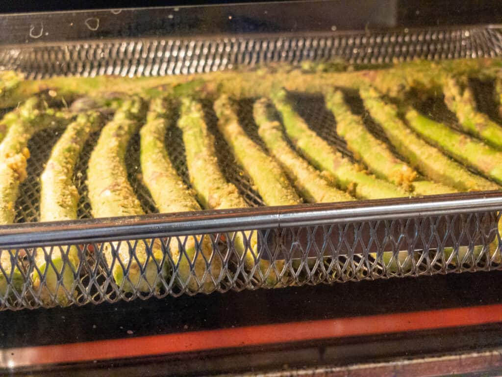 WFPB oil-free air-fryer asparagus cooking in the air fryer.