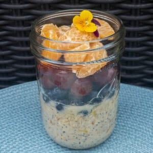Fruit Salad Overnight Oats in Jar Oats ingredients on bottom with blueberries, red grapes, and mandarin oranges on top.