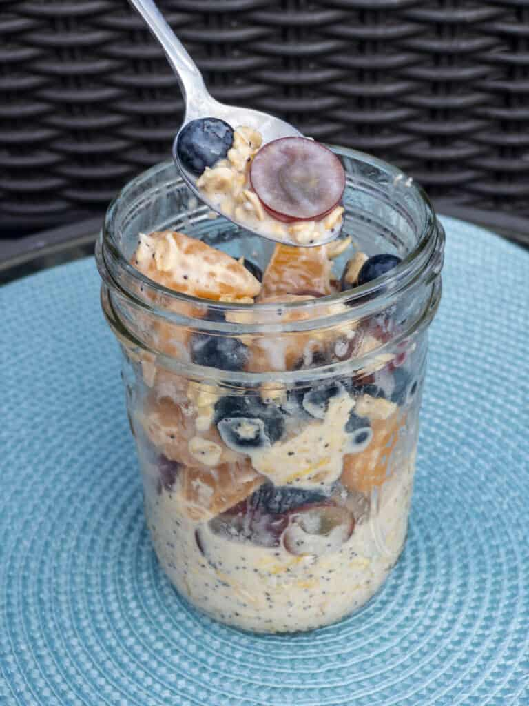 Fruit Salad Overnight Oats stirred in a jar and a spoonful lifted above the jar in a silver spoon.
