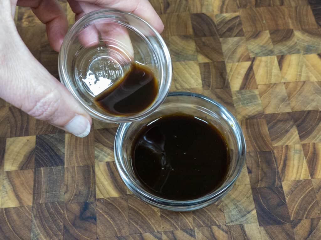 pouring liquid smoke into vegan worchestershire sauce