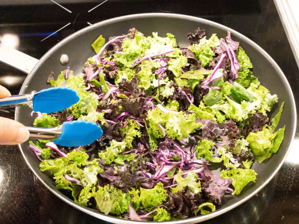 Greens with red cabbage added in nonstick pan with tongs