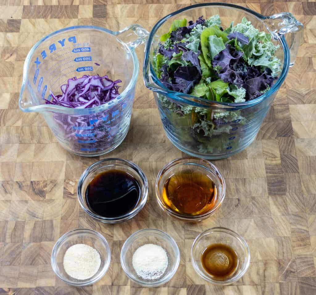 greens, red cabbage, soy sauce, maple syrup, liquid smoke, and spices on cutting board