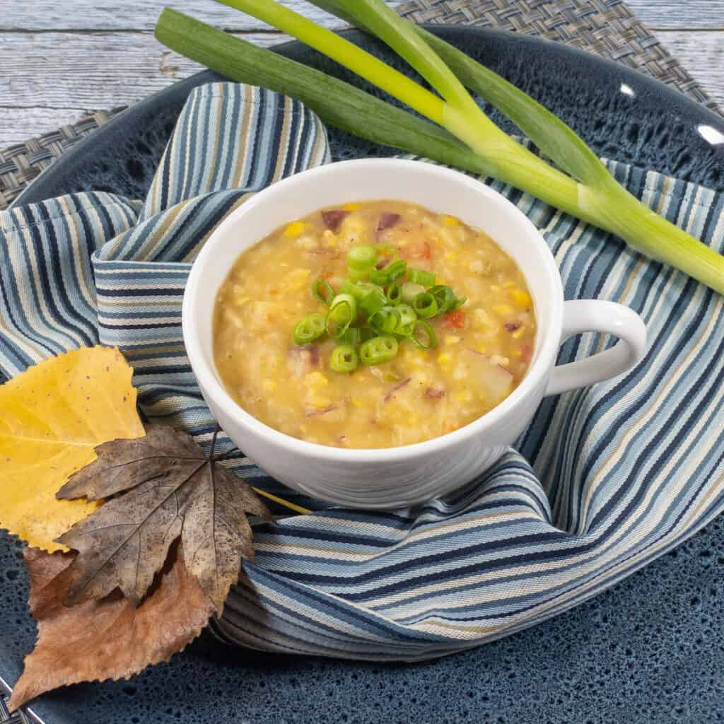 Creamy Rustic WFPB Sweet Corn Chowder in White mug over blue striped linen, fall leaves, and with green onion