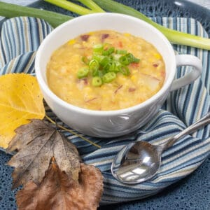 Sweet Corn Chowder in white mug over blue striped linen with spoon and leaves