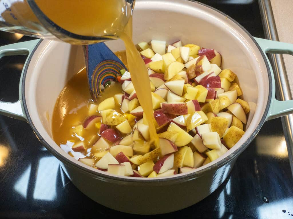 corn and potatoes added to the pot with vegetable broth being poured in