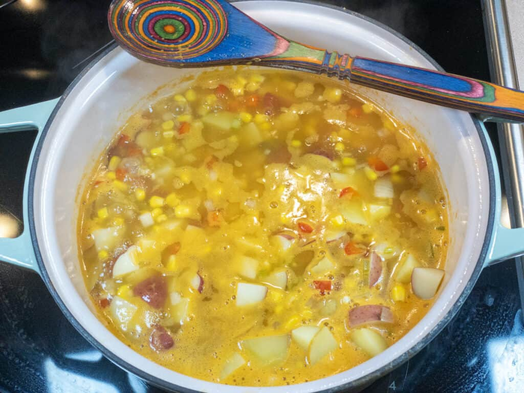 vegetables, potatoes, corn, and broth simmering in pot with brightly colored wooden spoon laying on top